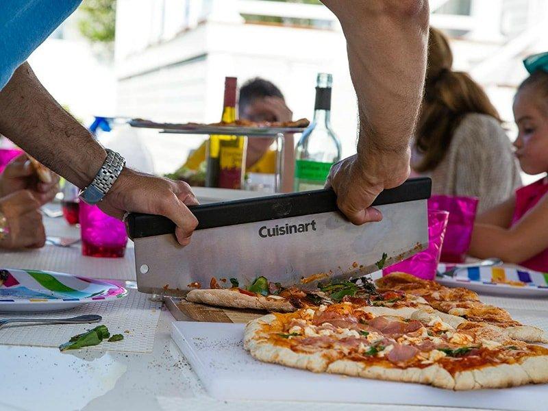 person cuttimg a pizza