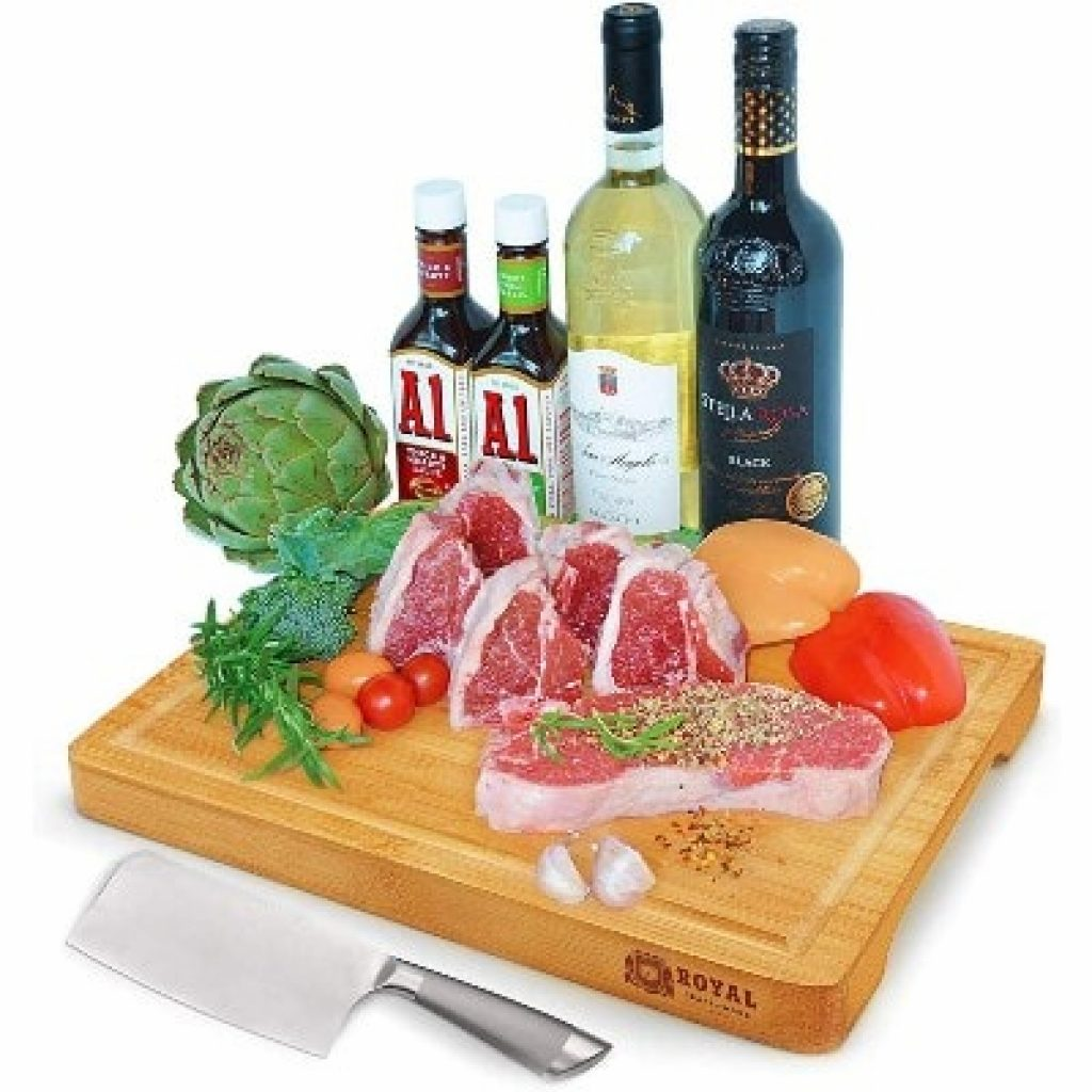 Organic Bamboo Cutting Board with Juice Groove with products on it on white background