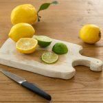 wooden cutting board with lemons on it